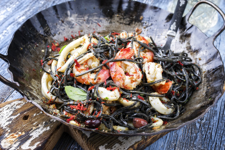 Italian linguine con tinta de calamari and prawns with olives as close-up on a wroth iron pan