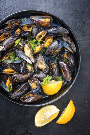 Traditional barbecue Italian blue mussel in white wine as top view in a casserole 免版税图像 - 103131738