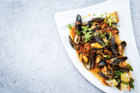 Traditional Italian blue mussel in white wine sauce as close up on a plate with copy space left Stock Photo