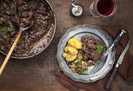 Fresh veal liver ragout in red wine sauce with fried potatoes and cabbage as top view on a plate Standard-Bild - 103114329