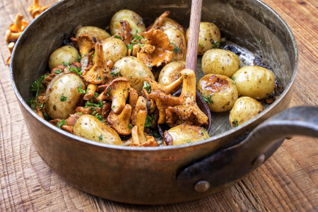Fresh fried chanterelle with potatoes as top view in a casserole Stock Photo - 103114330