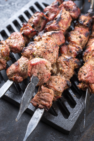 Traditional Russian shashlik on a barbecue skewer as top view on grillage