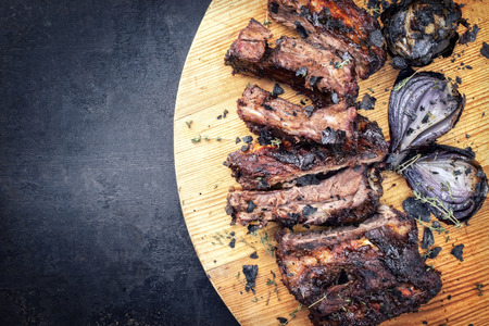 Barbecue caveman spare ribs St Louis cut with hot honey chili marinade and burnt onion as top view on a board  Reklamní fotografie