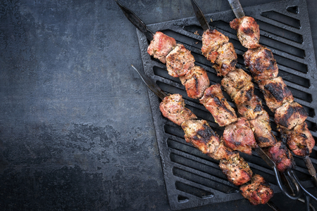 Traditional Russian shashlik on a barbecue skewer as top view on grillage with copy space left
