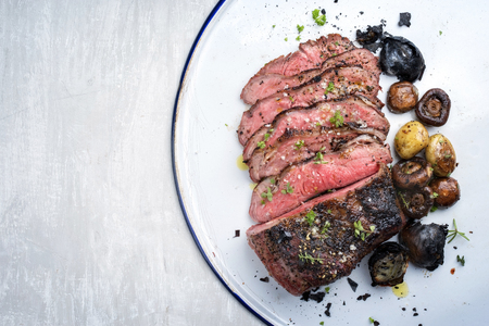 Barbecue caveman wagyu roast beef sliced with mushrooms and potatoes as top view on a tray with copy space left Stock Photo