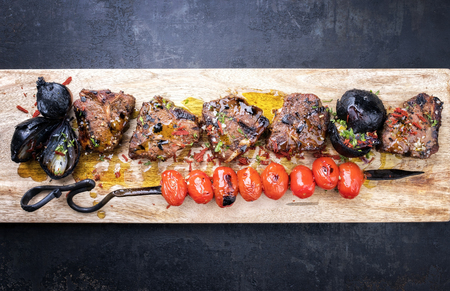 Barbecue t-bone lamb steak with carbonized onion and skewered tomatoes as top view on a cutting board