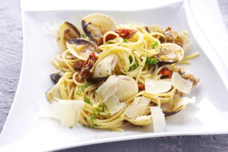 Spaghetti alle vongole with tomato pesto as close-up on a plate Banco de Imagens