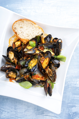 Traditional Italian blue mussel in white wine sauce as close up on a plate with copy space Stock Photo