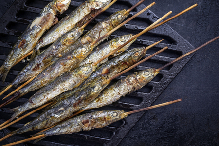 Traditional Spanish barbecue sardines on a wooden skewer as top view on a grillage Stockfoto - 104634433