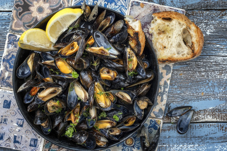 Traditional barbecue Italian blue mussel in white wine as top view in a casserole Standard-Bild - 103132518