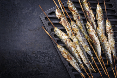 Traditional Spanish barbecue sardines on a wooden skewer as top view on a grillage Stockfoto - 104634467