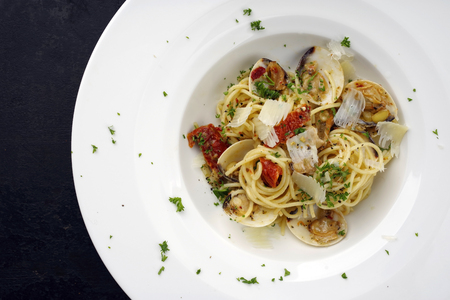 Spaghetti alle vongole with tomato pesto as top view on a plate with copy space left 版權商用圖片 - 103132166