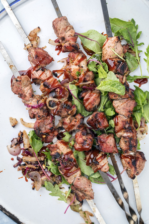 Traditional Russian shashlik on a barbecue skewer with roasted onion and lettuce as top view on tray Imagens