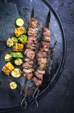 Traditional Russian shashlik on a barbecue skewer with vegetable as top view on old board with copy space right