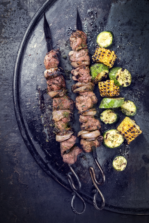Traditional Russian shashlik on a barbecue skewer with vegetable as top view on old board with copy space left Imagens