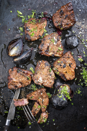 Barbecue t-bone lamb steak with carbonized onion and seasonings as top view on a rusty board Stock Photo