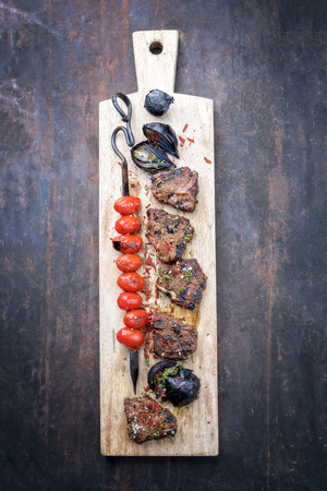 Barbecue t-bone lamb steak with carbonized onion and skewered tomatoes as top view on a cutting  board Stock Photo