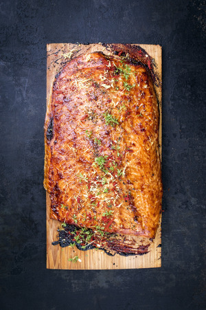 Barbecue salmon fillet marinated on cedar plank wood as top view