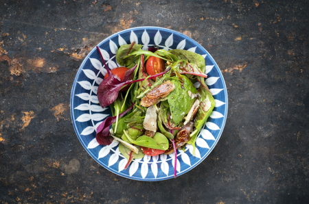 Traditional Italian lettuce with tomatoes and fig as top view on a plate with copy space Reklamní fotografie