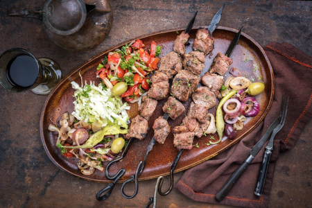 Traditional Turkish lamb kebab barbecue skewer with cabbage and tomato onion salad as top view on a plate Imagens