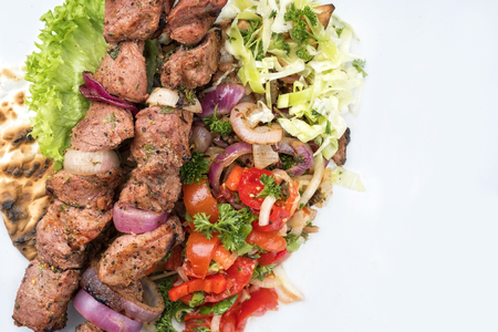 Traditional Greek souvlaki barbecue skewer with cabbage and tomato onion salad as close-up on white background with copy space right - covered Imagens