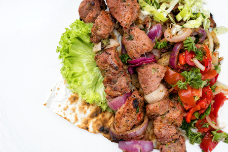 Traditional Greek souvlaki barbecue skewer with cabbage and tomato onion salad as close-up on white background - covered Stock Photo - 105530871