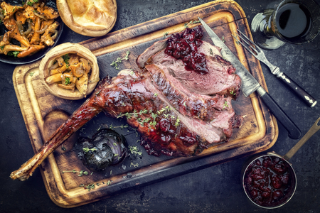 Marinated sliced barbecue aged leg of venison with chanterelles and Yorkshire pudding as top view on a rustic board Stock Photo