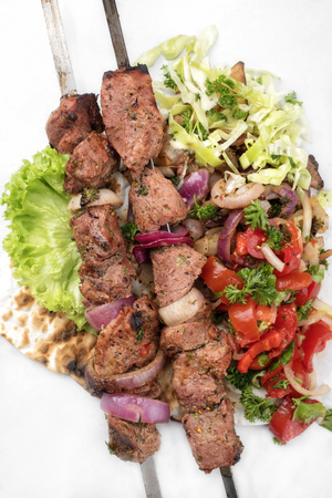 Traditional Greek souvlaki barbecue skewer with cabbage and tomato onion salad as close-up on white background - covered Imagens