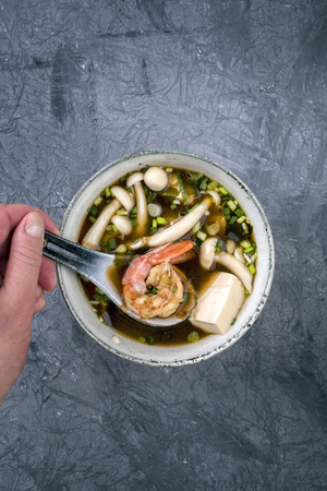 Traditional Japanese miso soup with king prawns and tofu as top view in a bowl with copy space Imagens