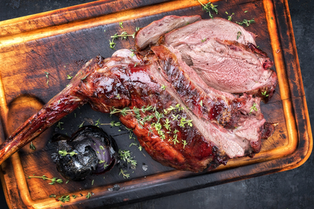 Marinated sliced barbecue aged leg of venison with onion as top view on rustic burnt cutting board Stock Photo