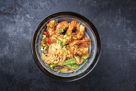 Traditional Thai Phak Kung curry with barbecue king prawns and noodles as top view in a bowl Stockfoto