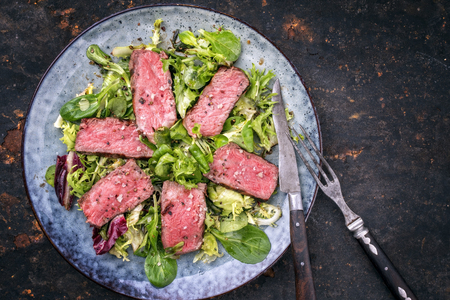Barbecue wagyu point steak slices with mixed lettuce as top view on a plate