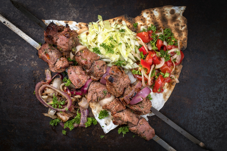 Traditional Greek souvlaki barbecue skewer with cabbage and tomato onion salad as top view on phyllo bread with copy space Imagens