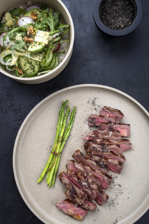 Traditional barbecue skirt steak sliced with green asparagus and salad as close-up on a plate Stok Fotoğraf