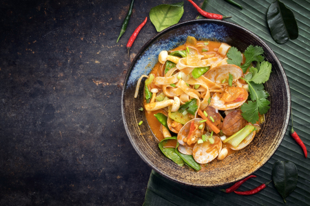 Traditional Thai kaeng phet red curry with clams and vegetable as top view in a bowl with copy space left