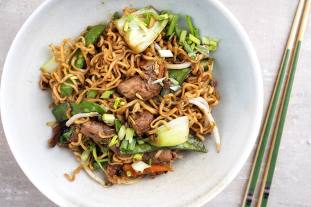 Traditional stir-fried Thai phat mama mie noodles with pork and vegetables as top view in a bowl