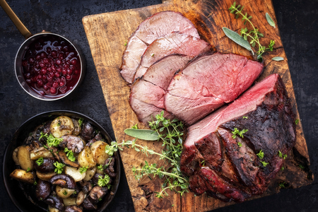 Barbecue dry aged haunch of venison with mushroom and potatoes as close-up on an old cutting board Stockfoto