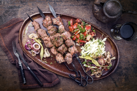 Traditional Turkish lamb kebab barbecue skewer with cabbage and tomato onion salad as top view on a plate - vintage Imagens
