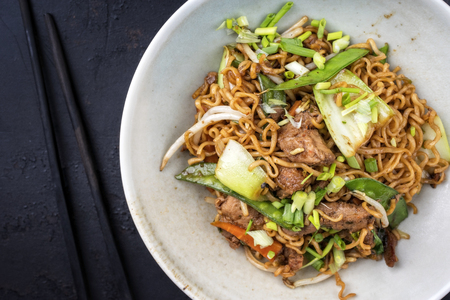 Traditional stir-fried Thai phat mama mie noodles with pork and vegetables as top view in a bowl with copy space left Stockfoto