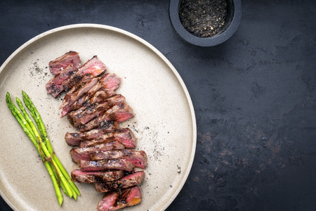 Traditional barbecue skirt steak sliced with green asparagus and smoked pepper as close-up on a plate Imagens