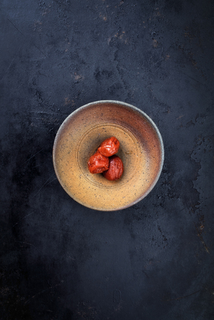 Traditional Japanese Umeboshi as close-up in a bowl on black background with copy space