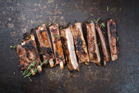 Barbecue spare ribs St Louis cut with hot honey chili marinade sliced as top view on an old rustic board Stock Photo