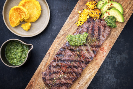 Barbecue dry aged wagyu flank steak with arepas corn, and chimichurri sauce as top view on a cutting board Archivio Fotografico