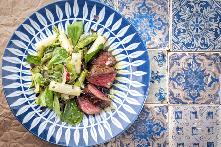 Traditional spring salad with barbecue dry aged sliced fillet steak and green and white asparagus as top view on a plate with copy space right