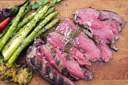 Traditional barbecue dry aged sliced roast beef steak with green asparagus and tomatoes as close up on a wooden board