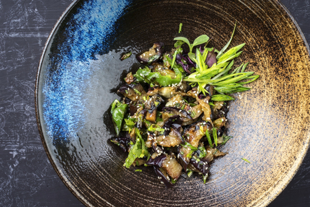 Traditional Asian eggplant ragout with scallions and sesame as top view in a bowl Stock Photo