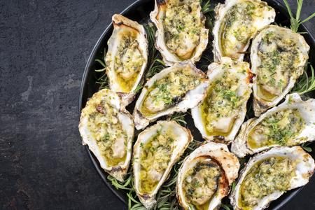 Barbacoa de ostras recién horneadas abiertas con ajo y hierbas que se ofrecen como vista superior en una bandeja con espacio de copia a la izquierda Foto de archivo