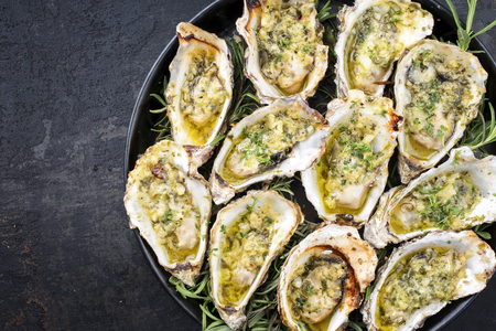 Barbecue overbaked fresh opened oyster with garlic and herbs offered as top view on a tray with copy space left Stockfoto