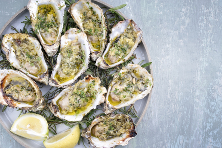 Barbecue overbaked fresh opened oyster with garlic, lemon and herbs offered as top view on a tray with copy space right