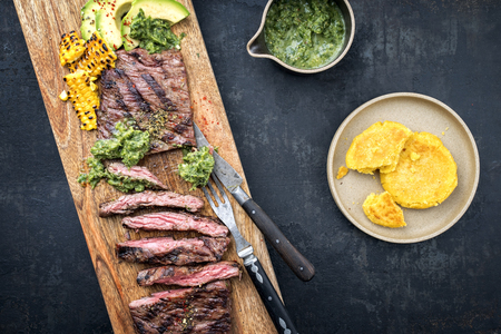 Barbecue dry aged wagyu flank steak with arepas, corn, and chimichurri sauce as top view on a cutting board